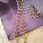 Set di collana e bracciale realizzato ad uncinetto con perle di vetro bianche e rosa